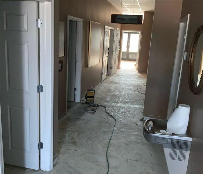 image of commercial building hallway with water damage before 3 foot flood cuts are made