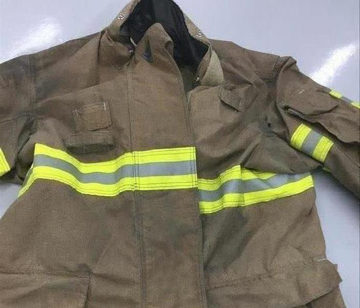 image of a local firemen's jacket looking dark and visibly showing dirt
