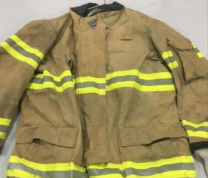 image of same firemen's jacket after it has been cleaned and restored, looking lighter