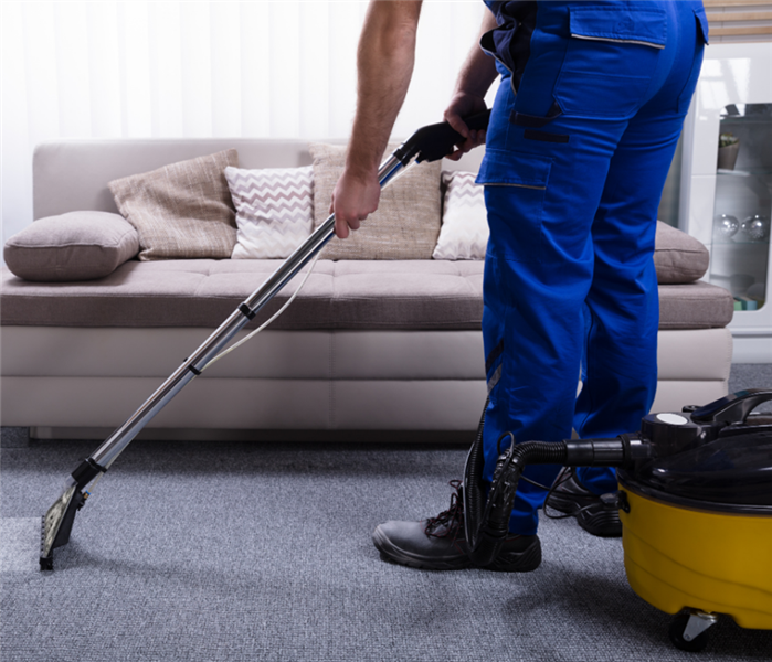 Picture shows a man cleaning carpet